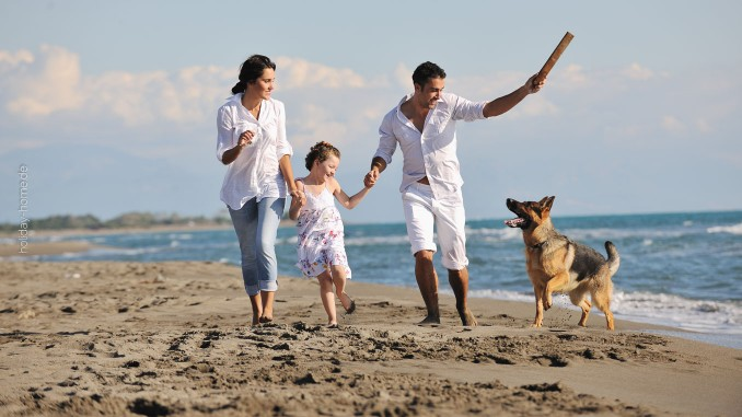 Glückliche Familie spielt mit Hund am Strand